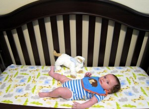 Charlie in his 4 in one crib, which has a higher setting for infants, lower setting for standers, and can be used as a toddler and big kid bed.